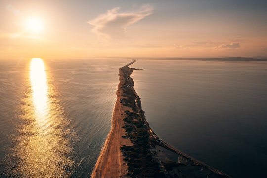 Long spit with sandy beach between sea and liman at sunset, aerial view from drone. Blagoveshchenskaya, Anapa region, Russia.