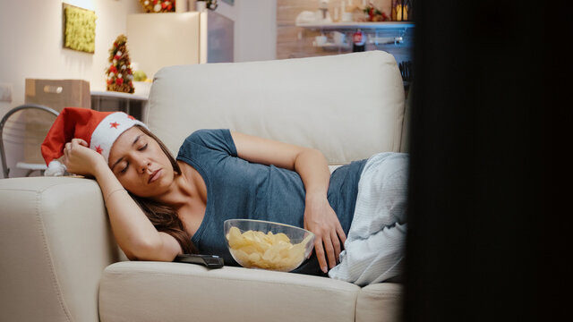 Adult with santa hat sleeping on couch at television. Festive person resting while looking at movie on TV, celebrating christmas eve alone on sofa with chips and snack. Tired woman