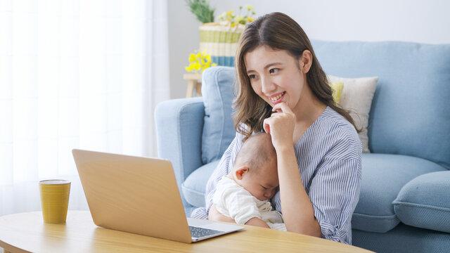 パソコンで仕事をするママと赤ちゃん(家族・ファミリー・育児・子育て・ビジネス)