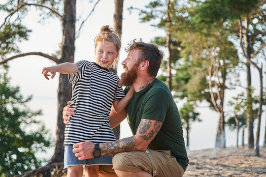 Father and girl are looking forward with happiness while sitting at the forest