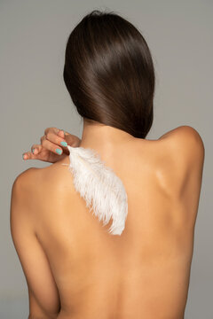 young woman caressing her shoulder with white feather