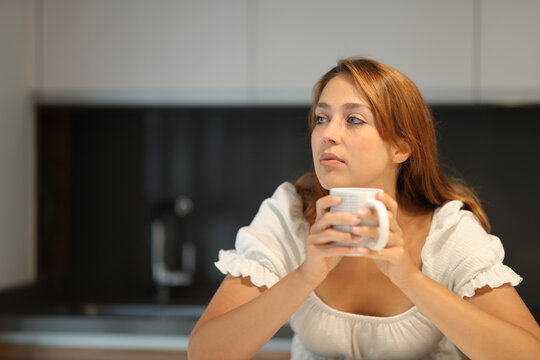 Pensive woman looking away holing cup at home