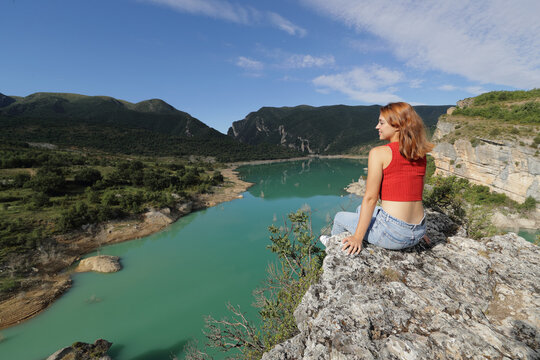 Woman contemplating views of a lake in a cliff