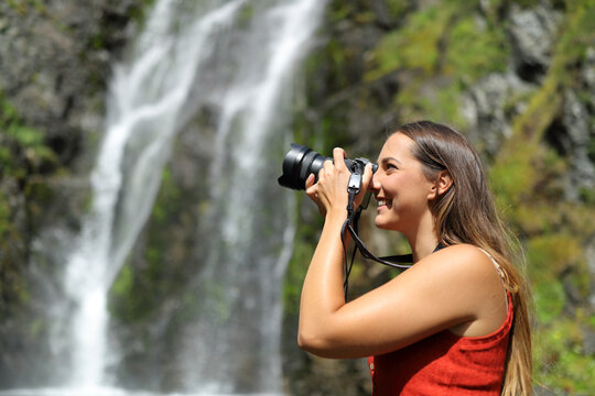 Woman taking photos with mirrorless camera in nature