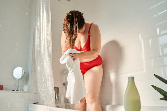 Female wiping her hair with towel after shower while having beauty procedures