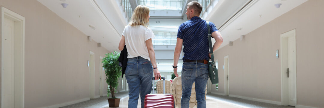 Man and woman walk with suitcase through hotel lobby