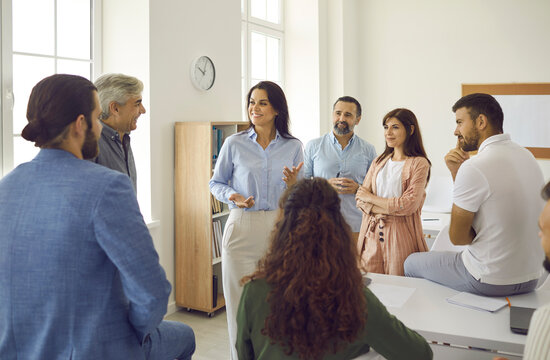 Group of happy corporate employees having an interesting meeting with a female team leader or business coach. Smiling young woman talking to a group of people during a workshop in a modern office