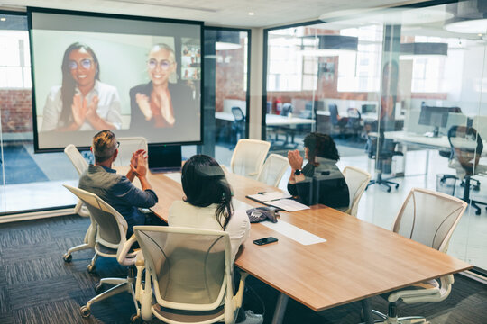 Creative businesspeople clapping during a video conference