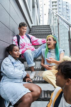 Friends sitting on metal stairs and resting
