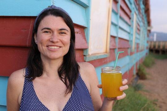 Beautiful woman drinking organic juice at the beach