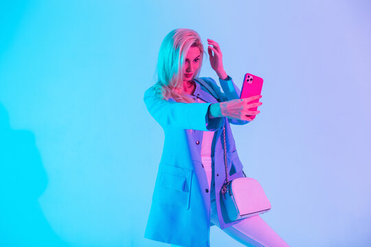 Stylish beautiful blonde woman in a fashion business suit look with a jacket and a handbag takes pictures of herself on a smartphone in the studio against a neon pink light. Creative selfie