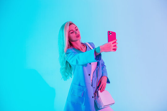 Beautiful young woman in fashion clothes with a stylish bag makes a selfie photo on a smartphone on neon pink light in the studio
