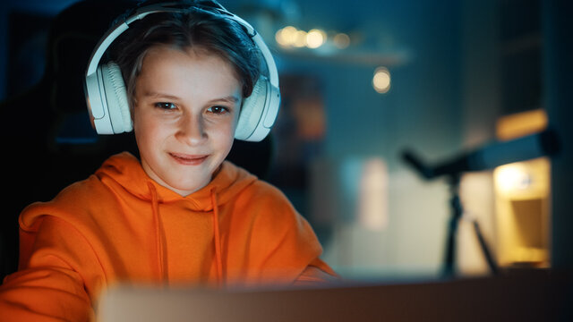 Smart Young Boy in Headphones Using Laptop Computer in Cozy Dark Room at Home. Happy Teenager Browsing Educational Research Online, Chatting with Friends, Studying School Homework.