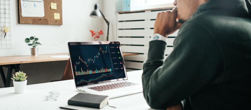 Investing in stock exchange market. Black man working remote using laptop. Wide screen