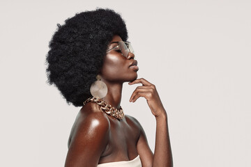 Obraz Side view of beautiful young African woman in golden jewelry keeping eyes closed and touching face - fototapety do salonu