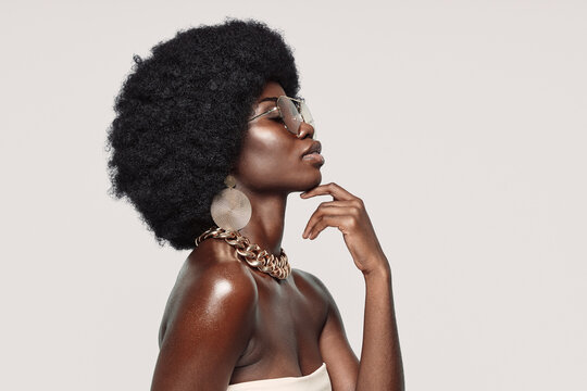 Side view of beautiful young African woman in golden jewelry keeping eyes closed and touching face