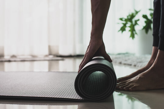 .Young woman practicing yoga and meditating. Woman hand is rolling up and preparing exercise mat for practice online yoga class in the morning at home.