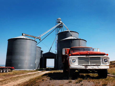 Old Red Work Truck Parked in Front of Several Steel Grain Silos on Farm