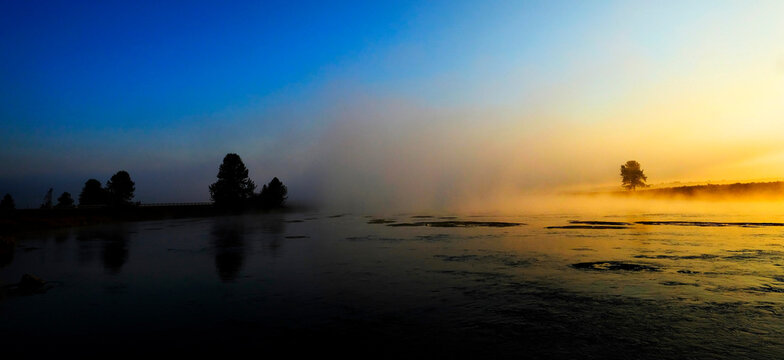 Morning Sunrise with Trees and River Blue Sky and Glowing Mist