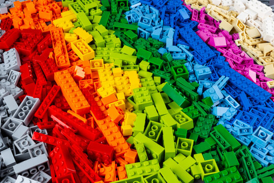 top view pile of many various colorful rainbow colored stackable plastic toy bricks. childhood education development concept