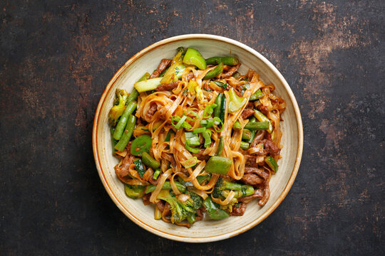 Oriental noodles, top view. Beef fried on a wok with rice noodles, green beans, zucchini, pak choi and green peppers in spicy soy-oyster sauce, in a bowl, on black stony background. Thai cousine dish.