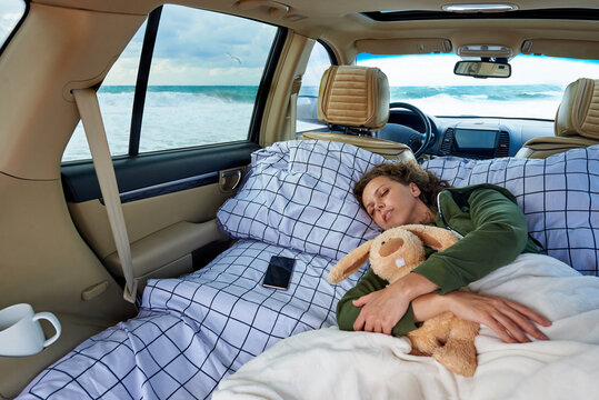 A young woman sleeps in a hugging with a stuffed rabbit in the car by the ocean.