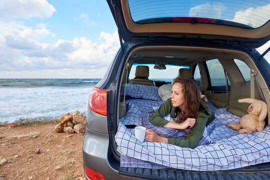 A young woman awake in the morning in a car by the ocean.