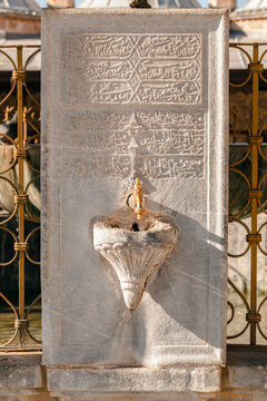 Close-up photo of a faucet on a big old marble stone with engraved old arabic writings in Mevlana Mausoleum in Konya, Turkey.