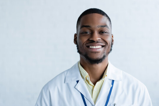 young and cheerful african american doctor looking at camera on white