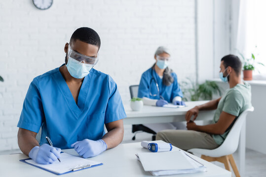 african american doctor writing on clipboard while burred colleague working with patient