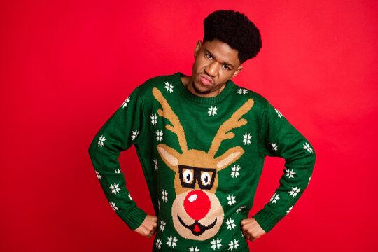 Photo of serious strict guy hands hips frowning face look camera wear christmas sweater isolated on red background