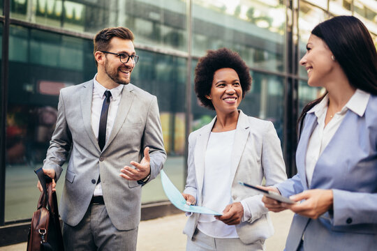 Three young business people talking to each other while walking outdoors.