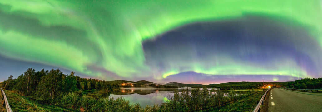 Wide Panorama Aurora borealis, Northern green lights with lot stars in the night sky over mountain lake, mirrored reflection in water, night mist. Night road, Joesjo, Northern Mountains, Sweden