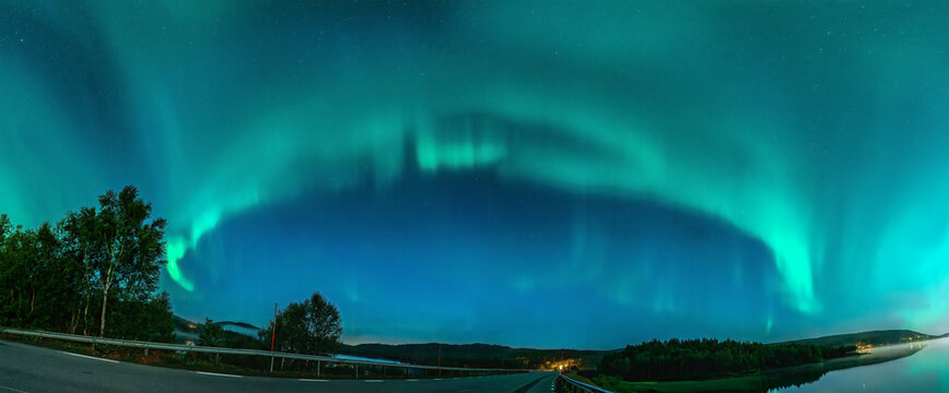 Panoramic Aurora borealis, Northern green lights with lot stars in the night sky over mountain road in mountains, mirrored reflection in water, night mist. Joesjo, Northern Sweden