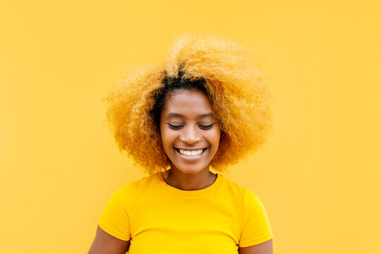 Curly hispanic young woman standing over yellow background with closed eyes - Happy afro american female smiling outdoors - Daydreaming concept