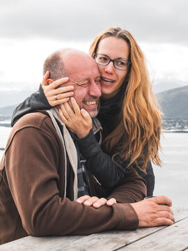 Caucasian middle-aged couple hugging in a park in front of a lake with mountains in the background
