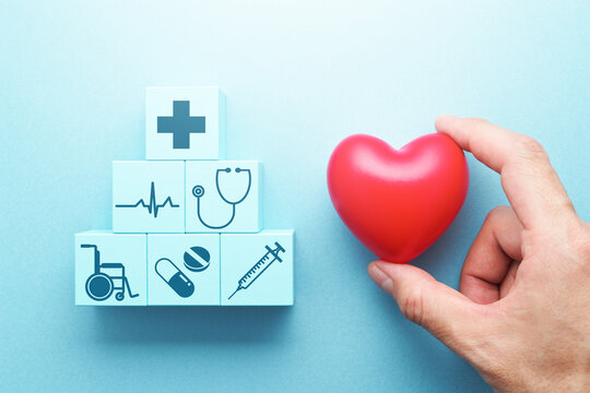 Medical care and insurance image. Hand holding heart.  Stacked medical icon blocks.