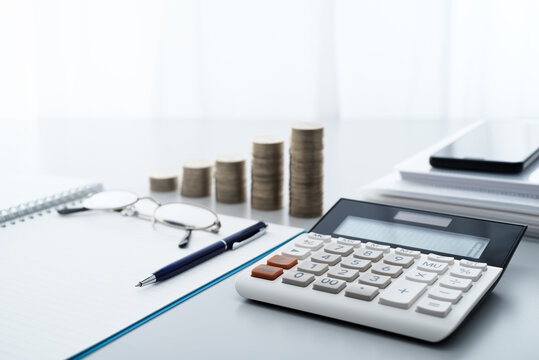 Household finance management and saving money. Calculator and stacking money.