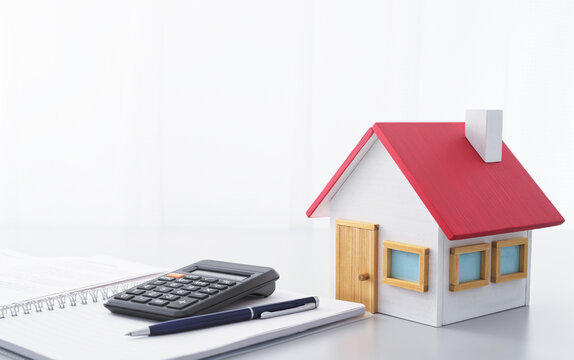 Housing finance. Calculator, notebook and miniature house.