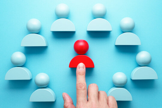 Selecting team leader. Hand pointing red person icon block.