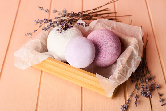 Box with bath bombs and lavender flowers on color wooden background