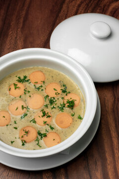 German traditional KARTOFFELSUPPE potato and sausage soup on wood table