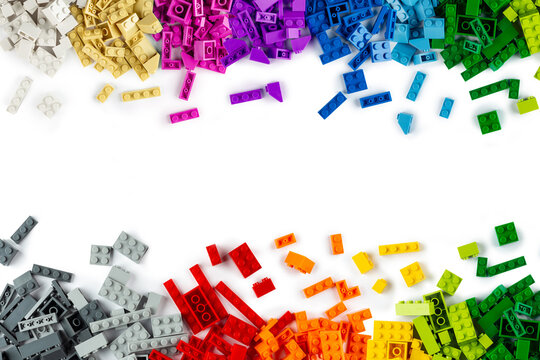 top view of border frame pile various colorful rainbow colored stackable plastic toy bricks isolated white panorama background.. childhood education construction concept