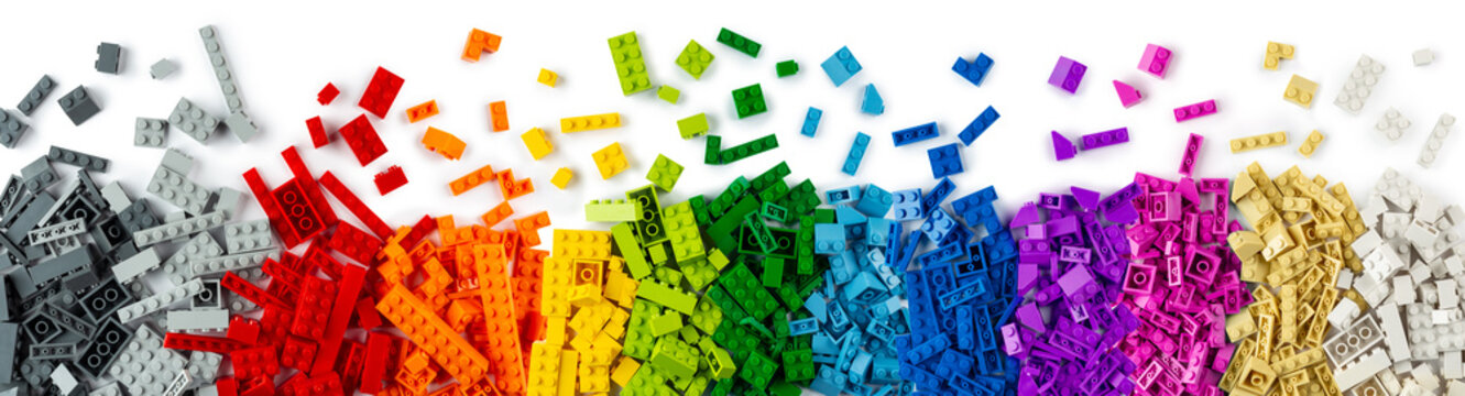 top view of wide pile various colorful rainbow colored stackable plastic toy bricks isolated white panorama background.. childhood education construction concept