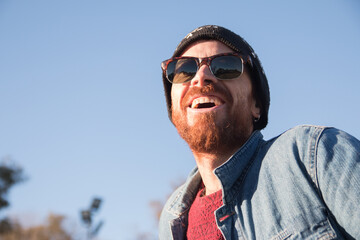 Closeup shot of a Caucasian handsome man with beard and sunglasses laughing under the sun