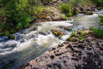 Fototapeta fast winding small mountain river flows among stones and gra obraz
