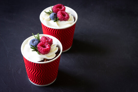 Dessert in a cups with cream cheese ,raspberries and blueberry, black background