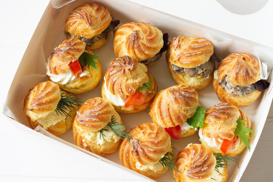 Profiterole staffed  with cream cheese mushrooms and  tomatoes. Food delivery, delivery box.Cheese profiteroles, profiterole buffet