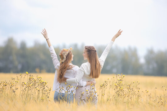 two girlfriends in an autumn field happiness / two young women hugging in a field, happiness friendship