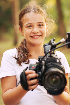 Cute girl shooting a video with a professional video camera